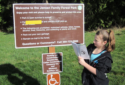 Child reading a park rules sign
