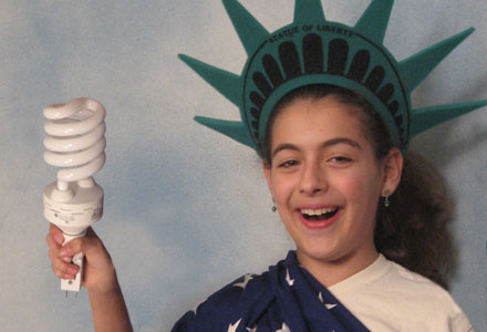 Child dressed as Statue of Liberty holding energy efficient light bulb