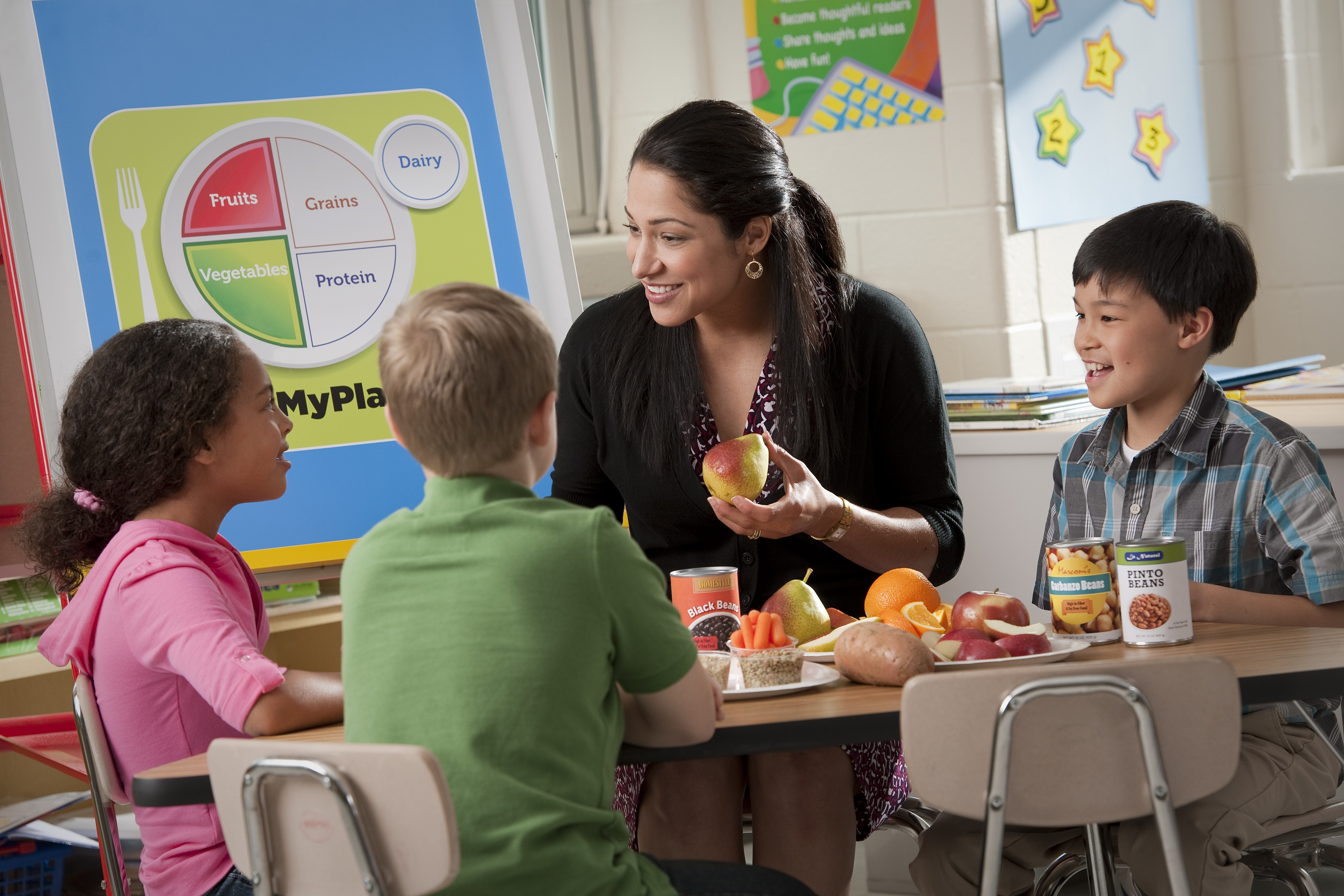 A hispanic teacher working with three students about nutrition