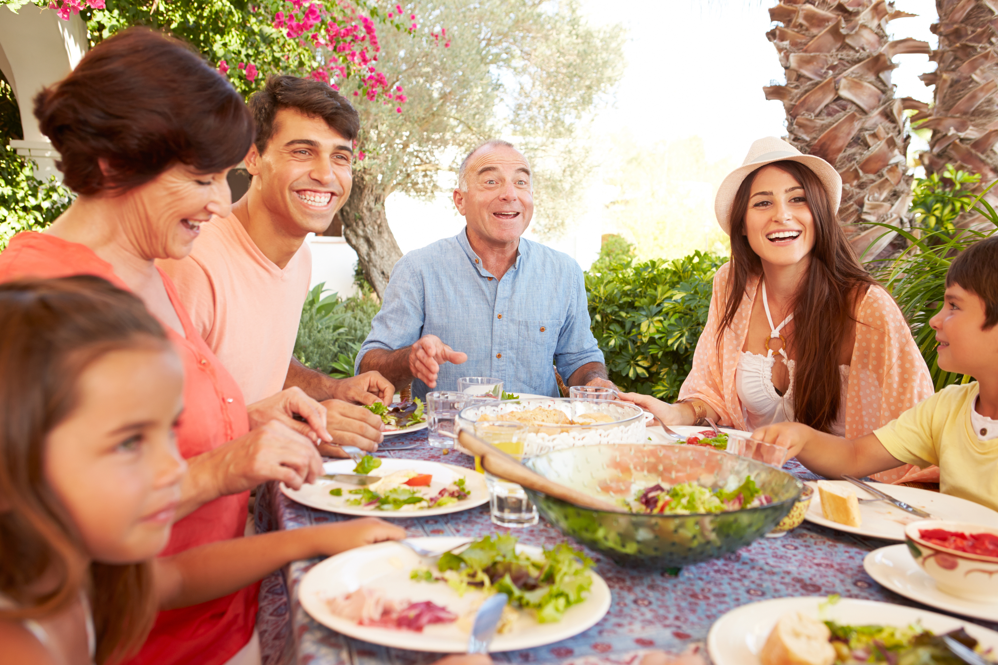 Hispanic family talking and smiling at an outdoor table with food