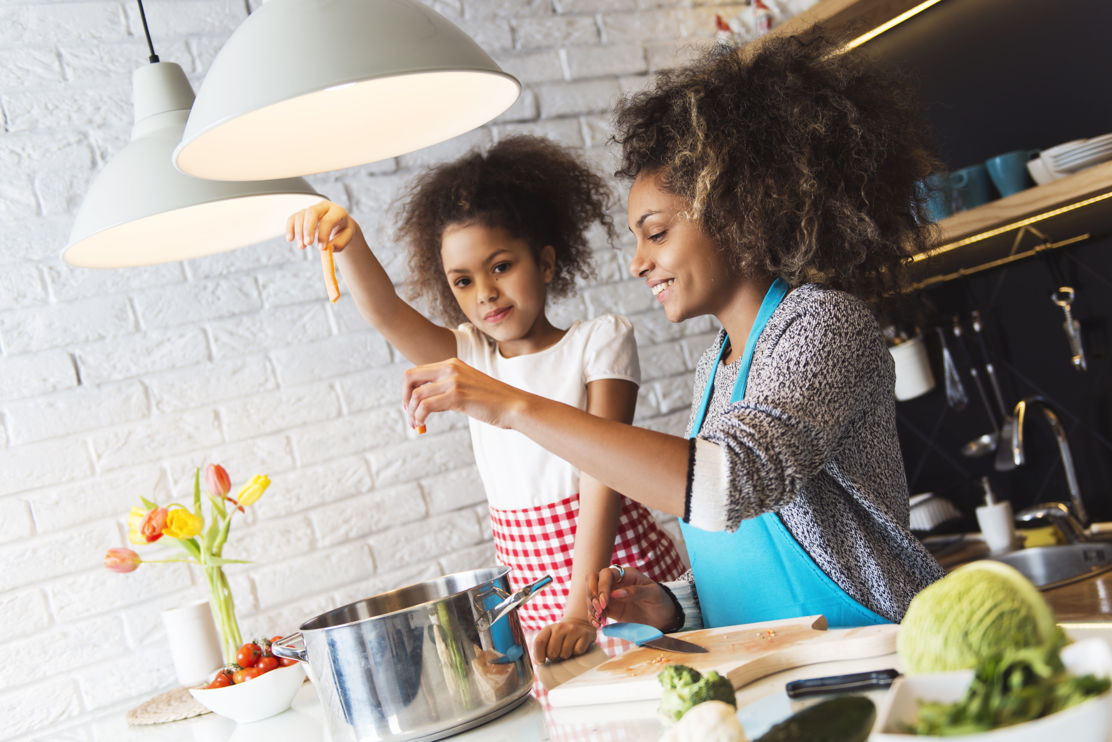 two African american women with lovely hair are making pasta in a kitchen with white brick walls