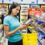 thin women reading a food label in a grocery store aisle