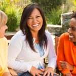 three women talking and smiling together sunny outside