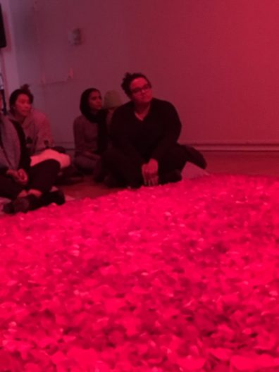 A group of students sit beside a deep bed of red rose petals.