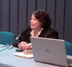 Vilma Navarro-Daniels delivering a talk while seated at a conference table.
