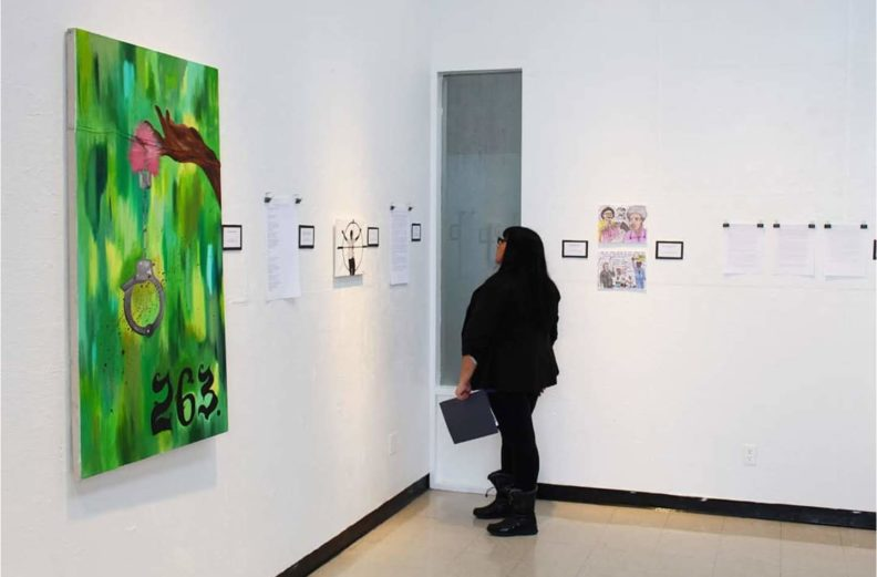 """""""Veronica Sandoval stands in gallery looking at art on the wall."""""""