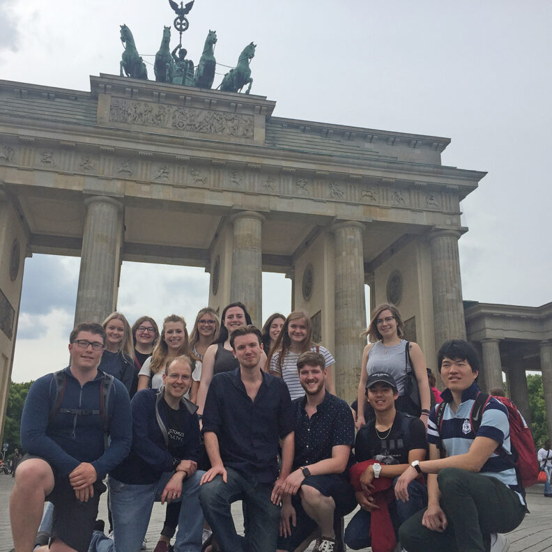 Students pose in front of a statue abroad.
