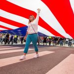 Woman standing under flag