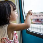 small child looking outside the window of a bus