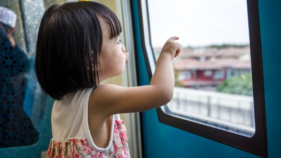 small girl looking outside the window on public transportation