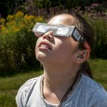Girl using solar eclipse glasses