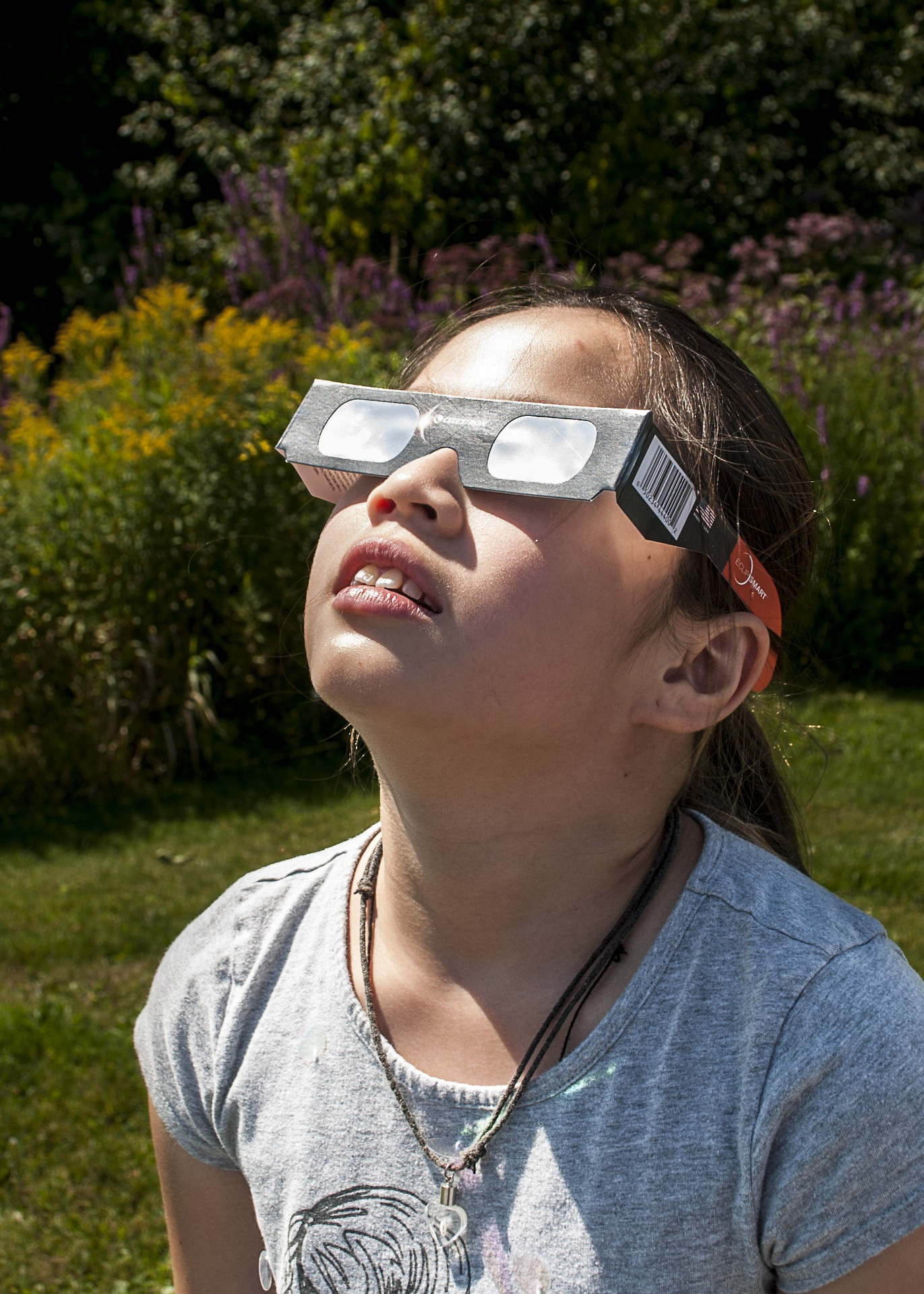 young girl looking at the solar eclipse with protective eye wear