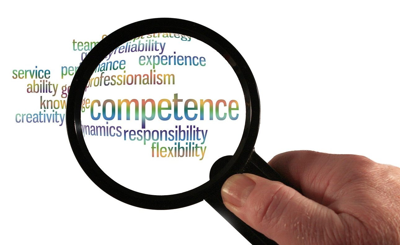 """Hand with magnifine glass over words"""" Competence, responsibility, flexibility, etc"""