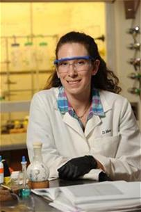student in labcoat and goggles next to test tubes and open textbook