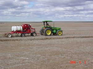 Tractor seeding a field with the LDRS Kile Drill in a field