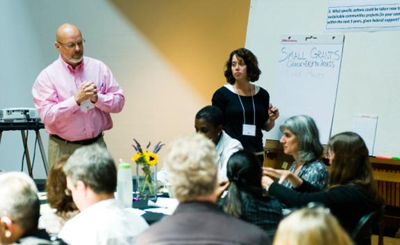 Two people speaking in front of a classroom of people.