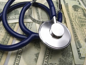 A stethoscope on a pile of dollar bills.