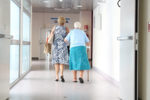 Two people, one with a cane, walking down a hallway.