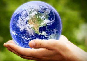 The globe of the earth held in human hand against a green, leafy backdrop.