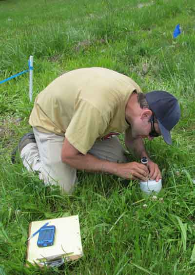A man bending over a soil monitor in a field.