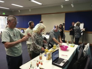 Teachers standing at a table, holding beakers of oil