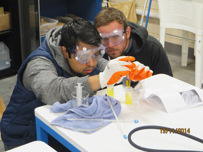 Two young men in safety goggles doing an experiment.