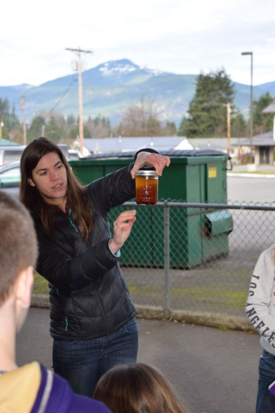 Marina demonstrating the step-by-step method to make biodiesel using oil from a nearby restaurant to a group of Darrington Middle School students.