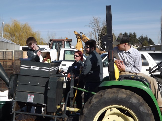 Students in the Plant Operations program at WWCC preparing food waste for composting with chipper.
