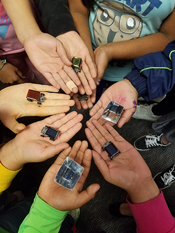 Young hands holding solar cars