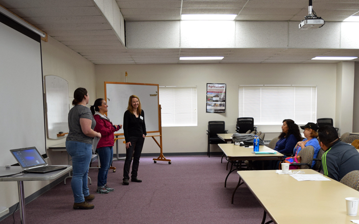 Yolimar Rivera Vázquez, Tatiana Giraldo, and Patricia Townsend (left to right) standing at the front of a WSU Extension classroom, teaching Latino members of the community who will then teach others about energy literacy.