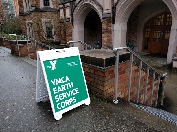 A YMCA Earth Service CORPS sign set up outside of Mary Gates Hall, pointing students in right direction to attend the workshop.