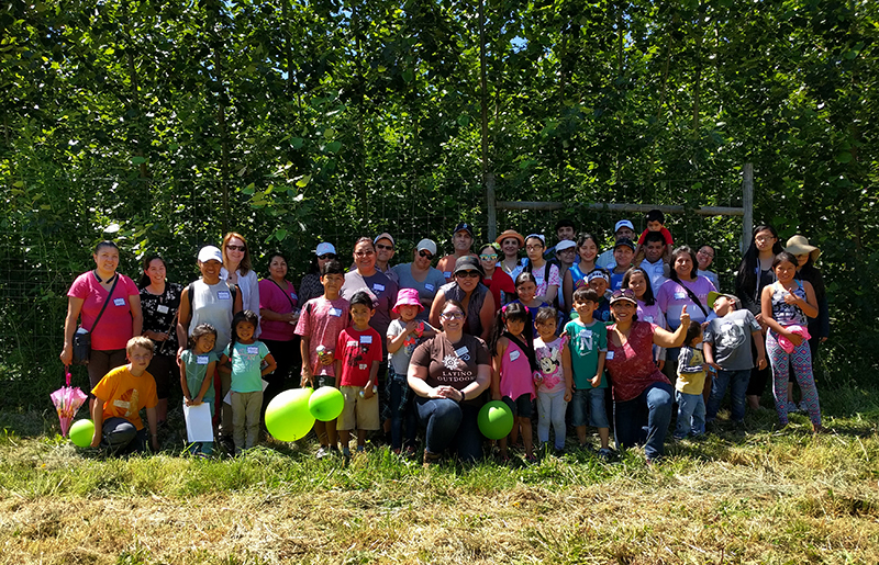 The entire field tour group: extension volunteers and Latino community members and their kids standing/sitting in front of the poplar trees.