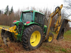 The green tractor with two large metal scythes on the back for ripping the field.