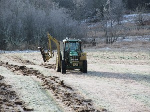 A closer image of the green tractor ripping rows into the Pilchuck field so that poplar trees can be planted.