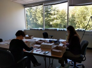 Two members of the AHB Extension team addressing and filling boxes of envelopes for a survey of policy makers in the Pacific Northwest.