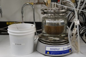 Then Enzymatic hydrolysis machine in the UW lab, filled with dark brown liquid, and a white bucket of SE Solids next to it.l