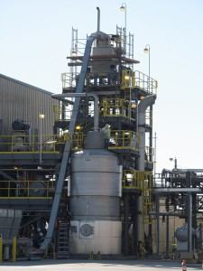 The outside of the Zeachem biorefinery, where a worker wearing jeans, a green shirt, and a hardhat can be seen.