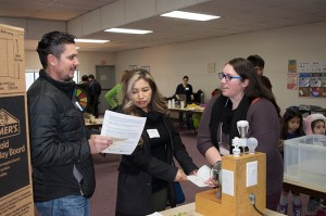 Extension professional Yolimar Rivera explains to a couple how to save energy and money by using LED lightbulbs.