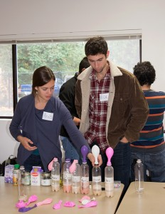 Two of the University of Washington volunteers setting up their table with plastic bottles and balloons to teach families how you can get power from yeast.
