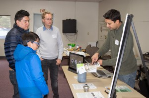 Two volunteers from Impact Bioenergy talk about composting with a father and his son.