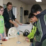 Two of the UW volunteers explaining wind energy to two boys with the help of a fan and a model of a wind turbine that powered small blinking lights.
