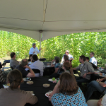 Brian Stanton addressing a group of more than twenty men and women seated at circular tables under a white tent during a field tour of the Jefferson site. The poplar trees, green and leafy in the summer, can be seen in the background.