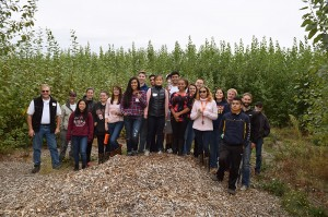 Rick Stonex and Marina Heppenstall posing with a group of 19 from Oregon State University atop a pile of wood chips with the green poplar trees behind them.