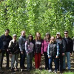Patricia Townsend, Tatiana Giraldo, and Yolimar Rivera Vázquez posing with Stephanie Leeper and her seven Energy Stewards (4 men, and 3 women) in front of the Pilchuck poplar trees on a sunny day.