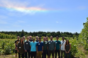 13 Western Washington University Students posing with their teacher in front of the poplars during their August field tour of the Pilchuck demonstration site. a rainbow stands out in the blue sky above the green trees.