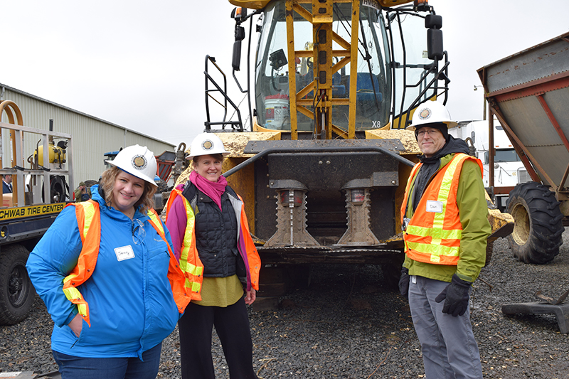 Three visitors (two women and a man) to the Jefferson demonstration site during its second harvest posiing in front of the yellow harvester.