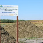 "After the harvest, piles of woodchips sitting next to and behind the sign that says Clarksburg Demonstration Site ""Poplar for Biofuels""."