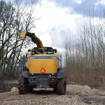 Rear view of the yellow harvester driving over the wood chips on its way to the next row of poplar trees.