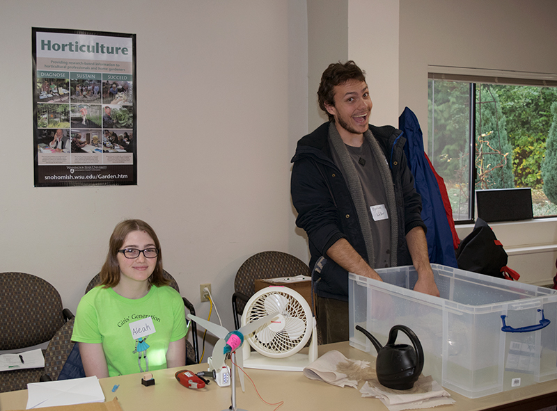 One volunteer sits behind the table waiting to demonstrate wind energy using a fan and turbine, while a second volunteer stands behind a tub of water and grins widely at the camera as he waits to demonstrate wave energy.