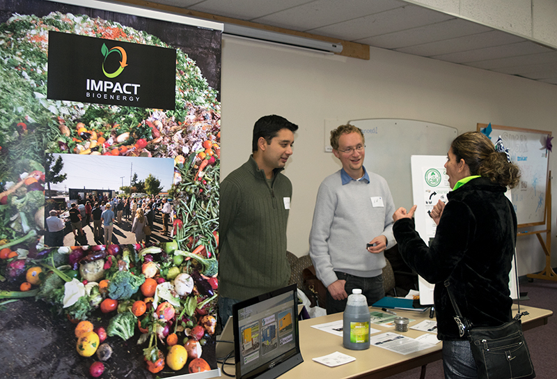 Two representatives of Impact Bioenergy talk with a woman who has stopped by their table. They have a laptop running a presentation and a large banner with a picture of many fruits and vegetables and the impact bioenergy logo.